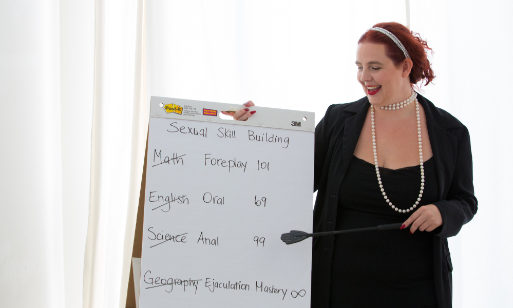 Gaia Morrissette is holding a riding crop, while pointing at white board. She is teaching a class