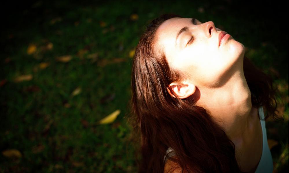 Women on her knees surrendering in nature. She looks like healing