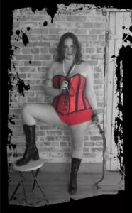 Gaia Morissette in a red corset holding a whip and riding crop