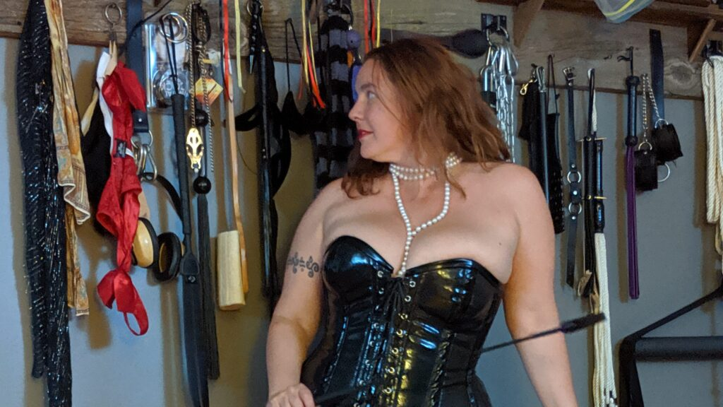 Pro Dominatrix Empress Gaia looking at her wall of BDSM tools holding riding crop. Bare feet wearing black PVC corset and red frilly panties